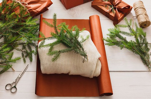 Wrapping christmas present gift on white wood background - Popular Inspiration — Designspiration