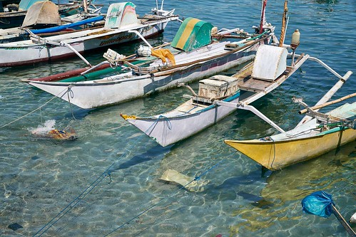 Boats and a boy in Bajo Bay harbor, Labuan Bajo, Flores Island, Indonesia