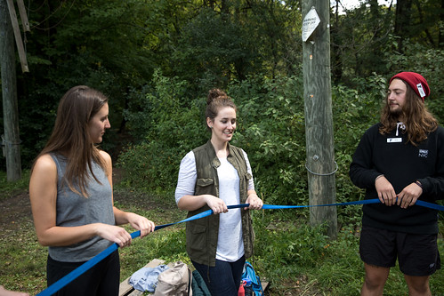 Hannah and camp counselor Huck hold a rope as Bailey speaks.