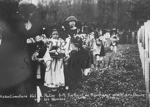Val du Pâtre (Schäfertal)/Alsacia, FRANȚA (9 aprilie 1924). Regina Maria a României Mari însoțită de tinere alsaciene, depune flori la mormintele eroilor Armatei Române, exterminați în lagărul german de gărzile lui Wilhelm al II-lea.