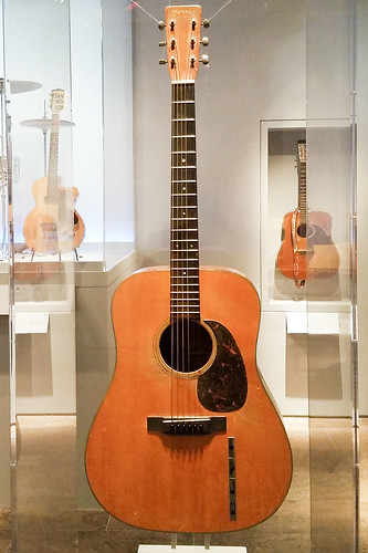 Elvis's guitar, flanked by George Harrison and Wanda Jackson -  Play It Loud: Instruments of Rock & Roll