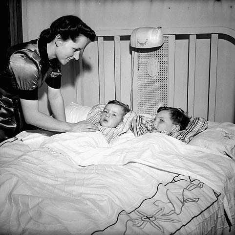 Mrs. Jack Wright tucking her two sons, Ralph and David, into bed at the end of the day, Toronto, Ontario / Mme Jack Wright bordant ses deux fils, Ralph et David, à la fin de la journée, Toronto (Ontario)