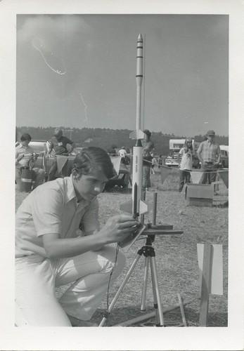 [Boy preps his model rocket for launch]