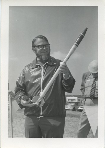 [Man poses with model rocket]