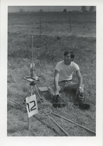 [Man sits in field next to model rocket launch pad]